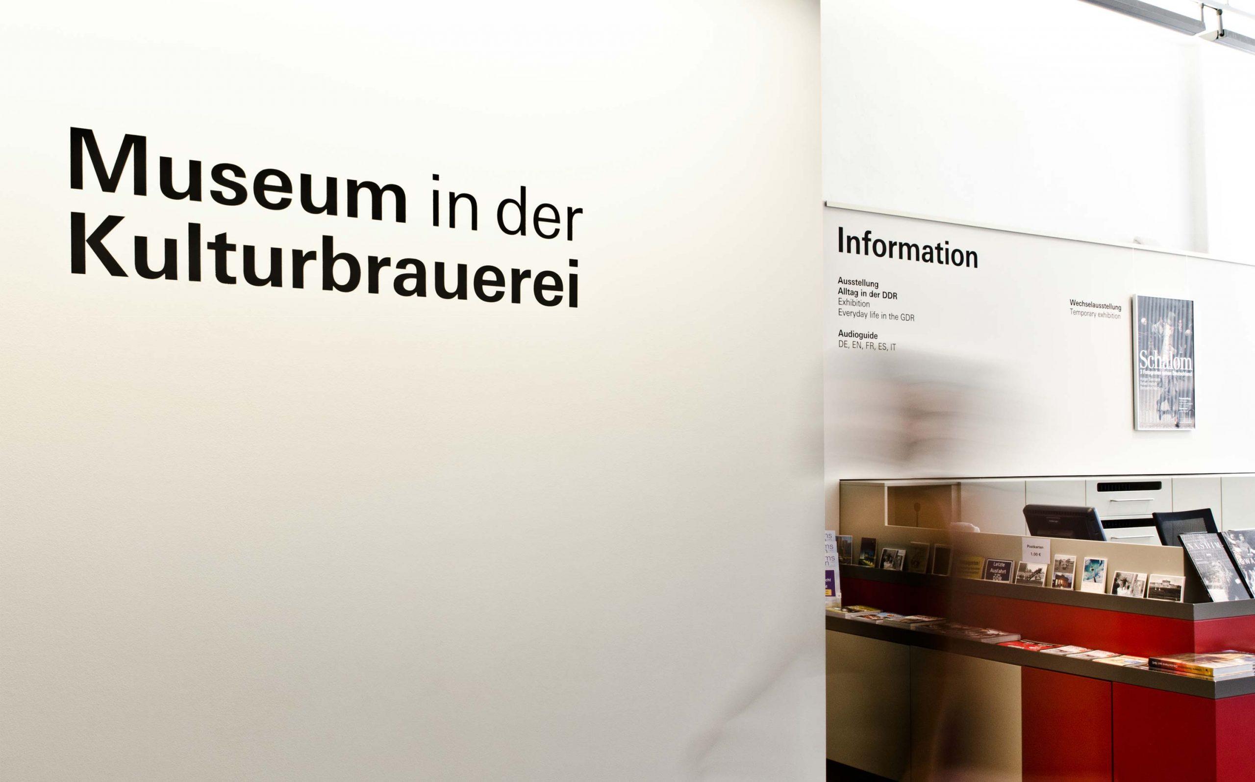 Eingangsbereich des Museums in der Kulturbrauerei mit Wandbeschriftung (Schablonierung), im Hintergrund die Informationstheke. Elemente: Schrift (Univers Regular und Univers Bold)