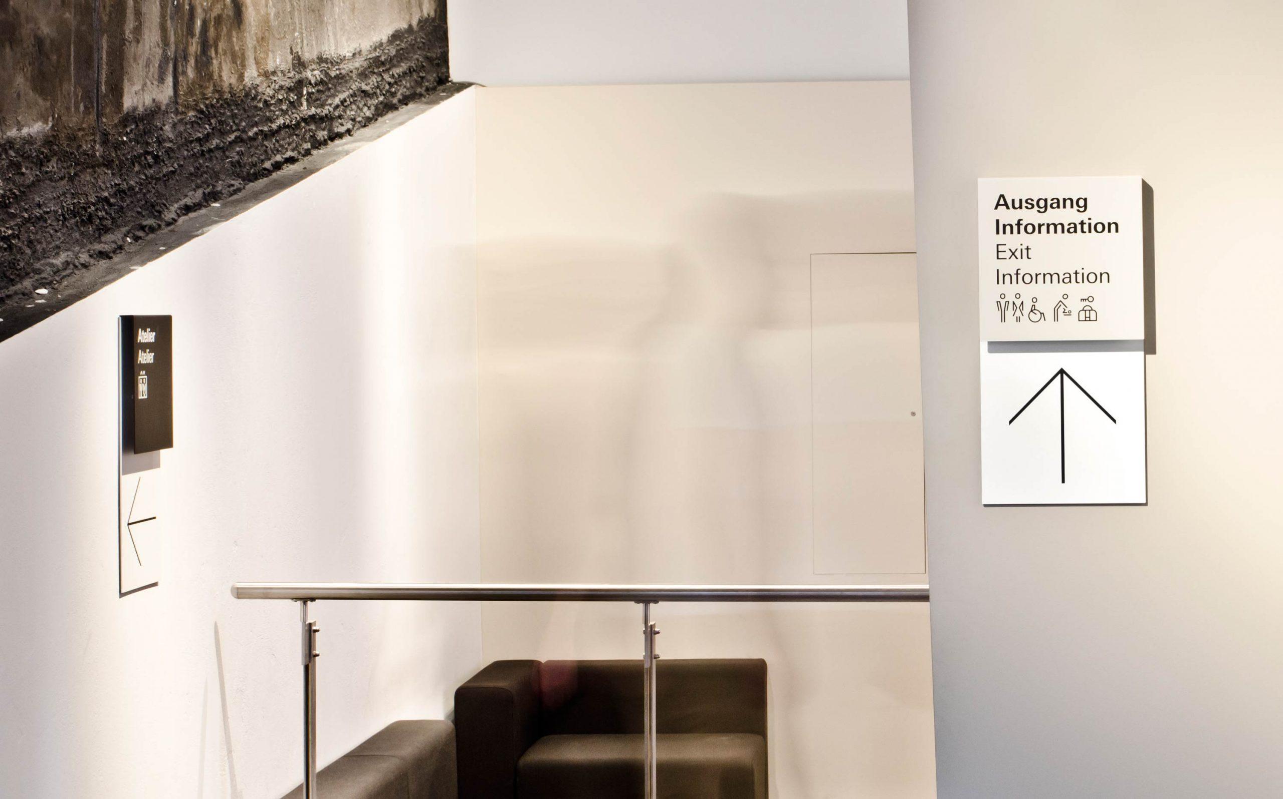 Leitsystem des Museums in der Kulturbrauerei, zwei Schilder, mit Primärinformation auf dem oberen und Richtungsangabe (Pfeil) auf dem unteren Teil, Direkt-Montage auf Innenwände bzw. historische Bestandswände (Denkmalschutz). Wegweiser, Farben: RAL 9002, RAL 9005 und weiß. Elemente: Schrift (Univers Regular und Univers Bold), Pfeile, Icons