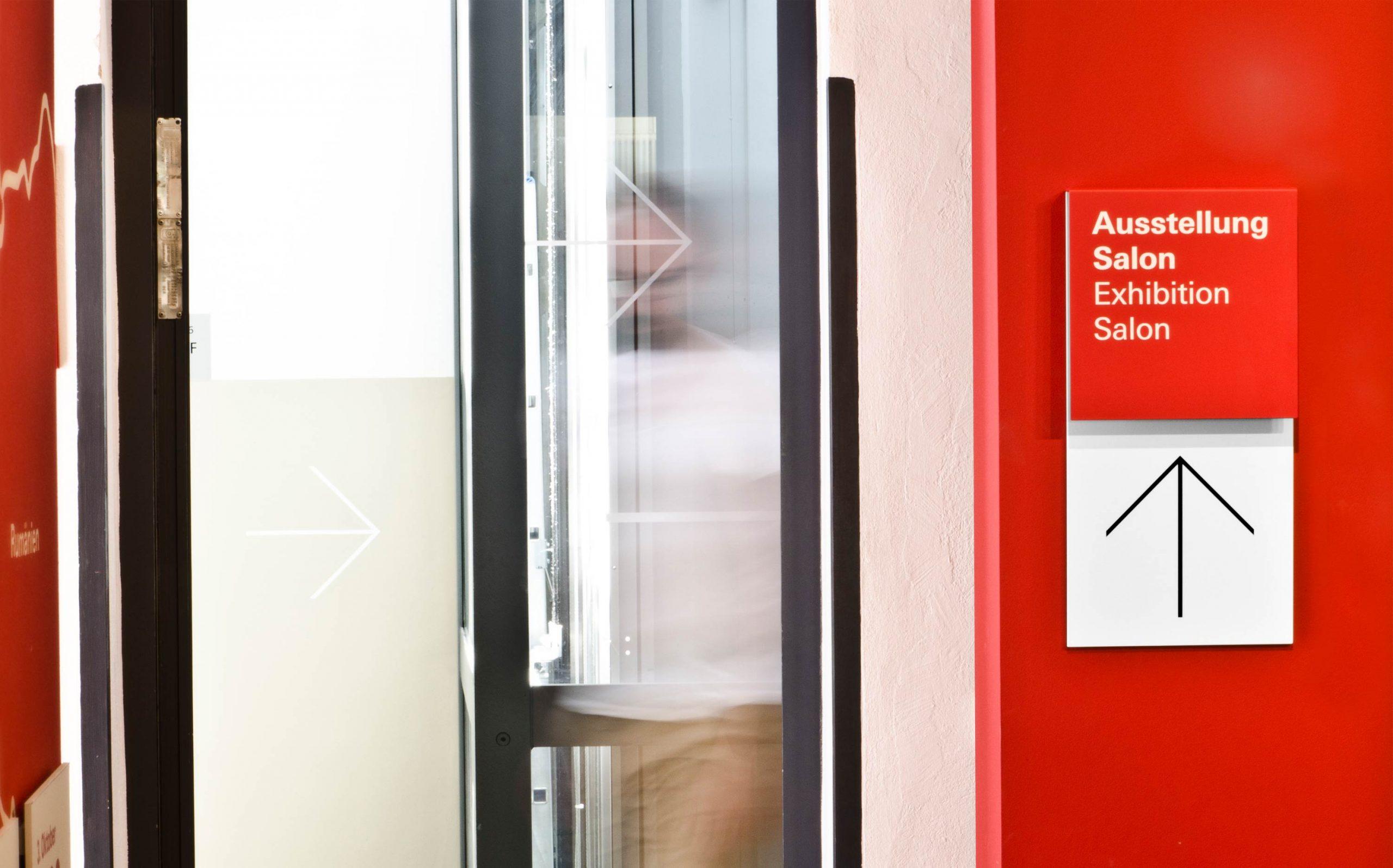 Leitsystem Museum in der Kulturbrauerei. Wegweiser mit Primärinformation (Ausstellung, Salon) oben und Richtungspfeil unten, rot-weiß. Direkt-Montage auf Vorbauwände. Farbe: RAL 3020 & weiß. Elemente: Pfeil, Schrift (Univers Regular und Univers Bold)
